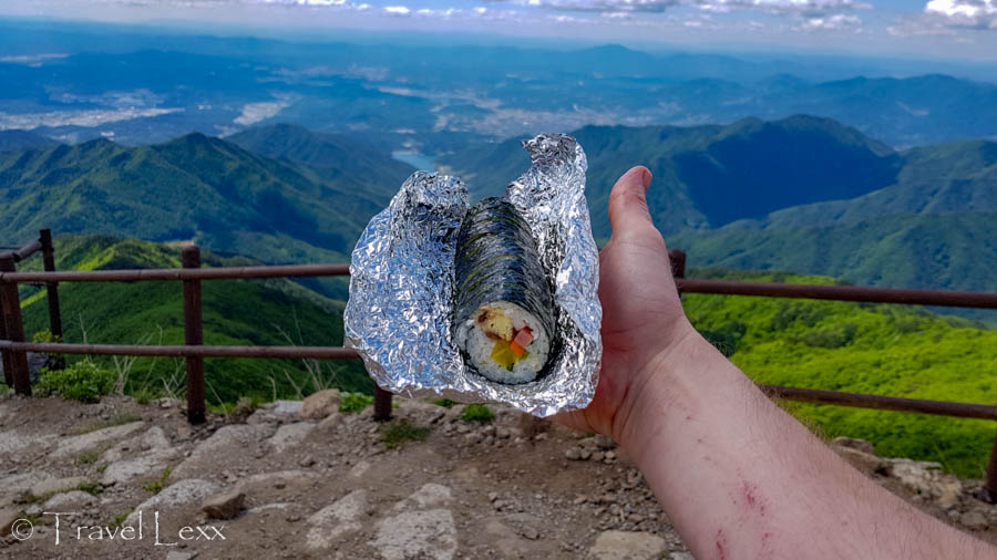 Man holding a kimbap in outstretched hand