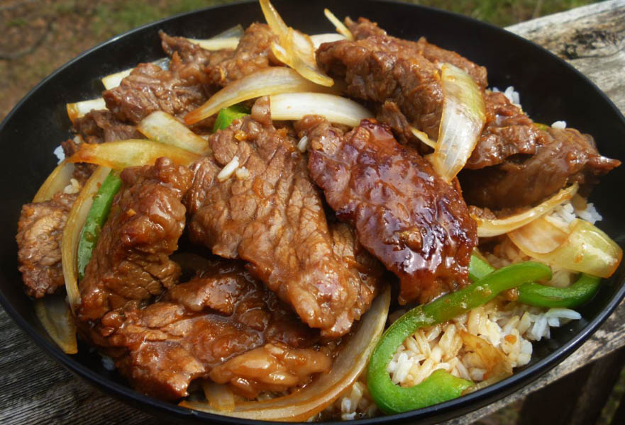 Strips of grilled meat, vegetables and rice in a dish