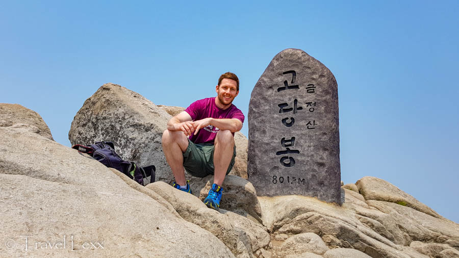 A man sitting in front of a stone marker at Godangbong Peak