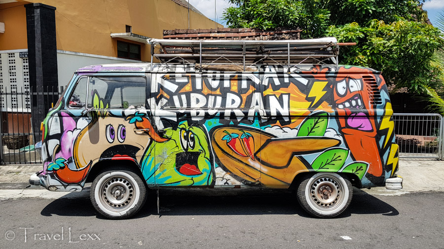 An old van adorned in colourful street art in Yogyakarta