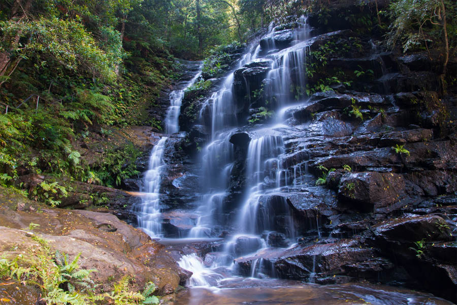 A waterfall cascading down rocks in the Valley of the Waters in Blue Mountains National Park