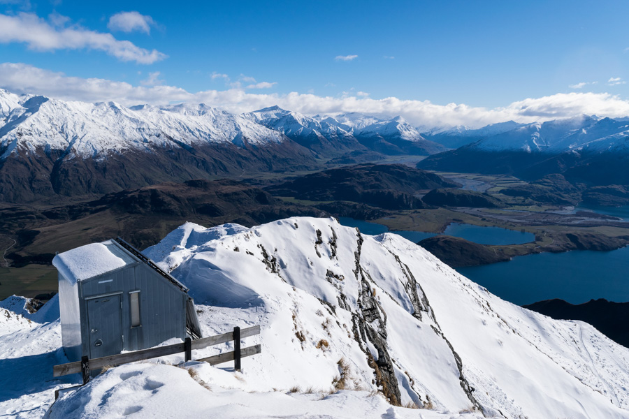 A small hut at the snow-covered summit of Roys Peak - a popular day hike near the city of Wanaka in New Zealand