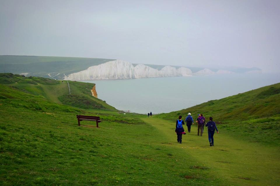 A group of hikers walking along a path towards the sea and white Seven Sisters cliffs in the distance near London