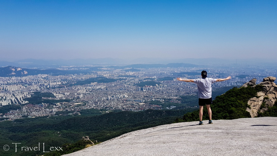 A man standing on a rocky outcrop overlooking a city of Seoul
