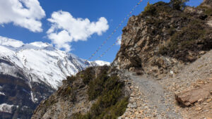 A path winding up a mountain side towards colourful flags with snow-capped peaks in the distance