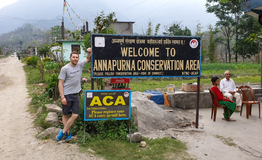 A hiker leaning on a sign near the start of the Annapurna Circuit between Besisahar and Bhulbhule