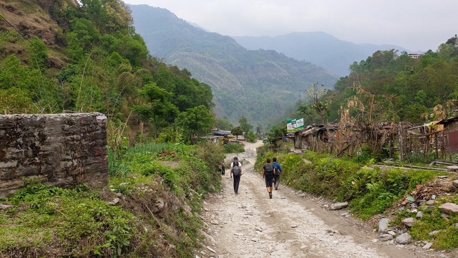 Three hikers walking along a dirt road between Besisahar and Bhulbhule