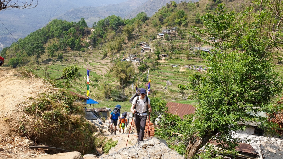 Hikers climbing a path towards a viewpoint in the village of Bahundanda