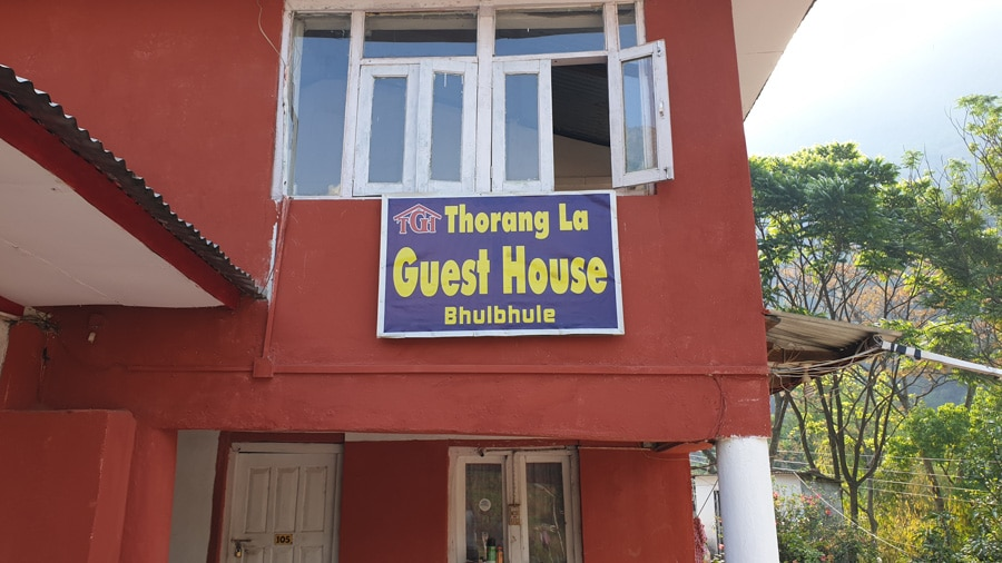 "A red building with a large ""Thorang La Guest House Bhulbhule"" sign"