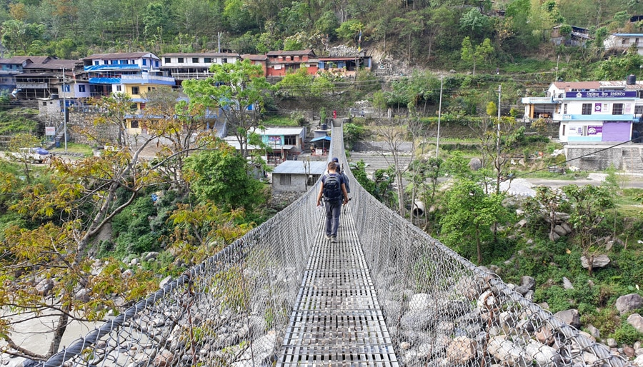 Hikers walking across a suspension bridge towards a Nepalese village
