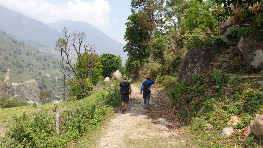 Two hikers walking along a path between Bhulbhule and Jagat along the Annapurna Circuit