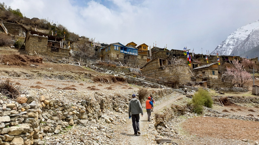 Hikers walking up a path towards Upper Pisang village with stone houses nestled on top of one another