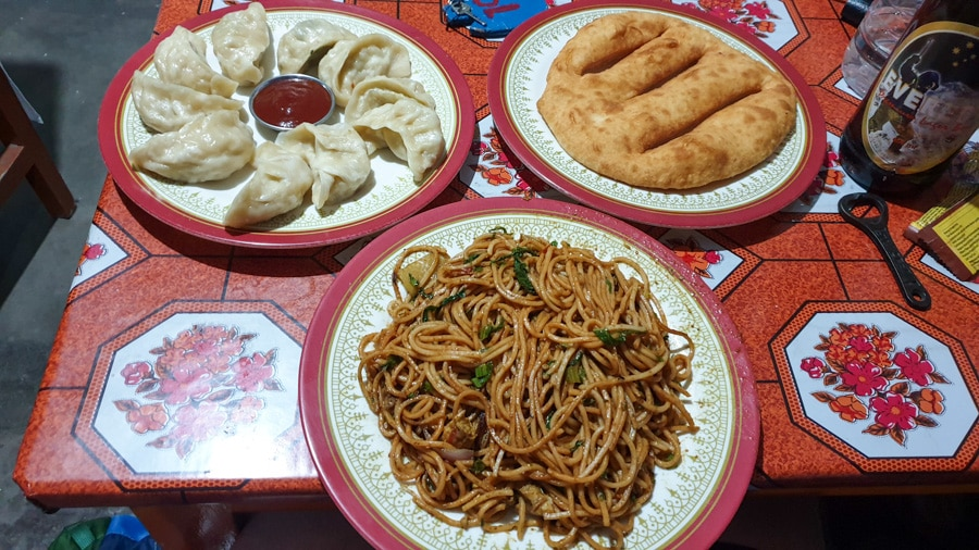 Three plates of fried noodles, momos and fried bread on a table
