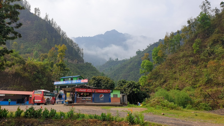 A parked bus at a service station at the foot of mountains on route from Kathmandu to Besisahar