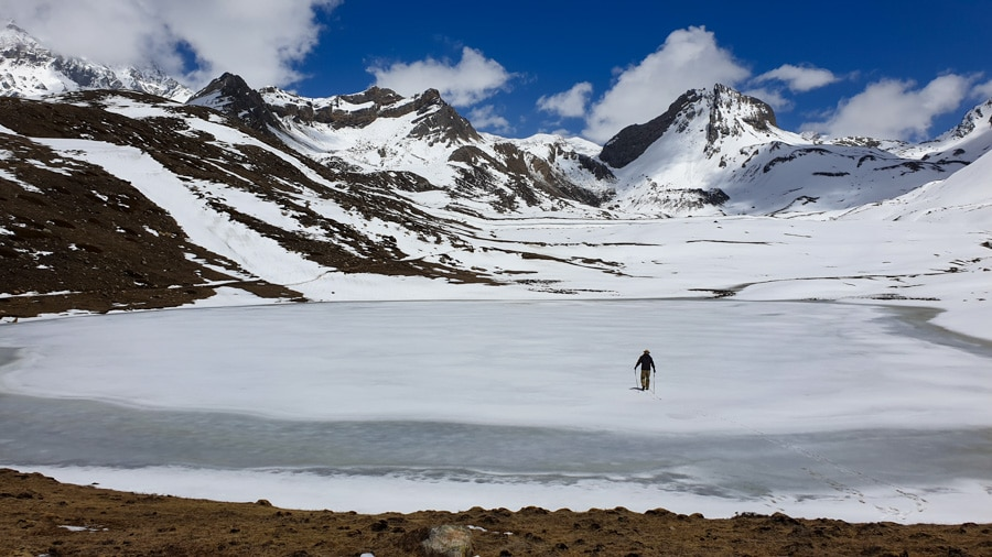 A lone hiker walking across the Ice Lake surrounded by mountains near Manang