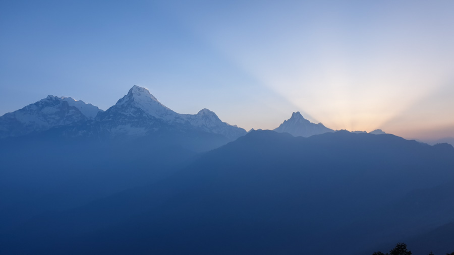 The sun rising behind mountain silhouettes at Poon Hill. This is one of the main highlights of the Annapurna Circuit itinerary
