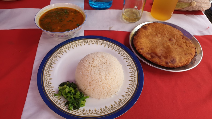 A plate of rice, a plate of a small round Tibetan bread and a bowl of red soup
