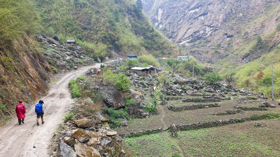 Hikers walking past fields and small houses along the Annapurna Circuit
