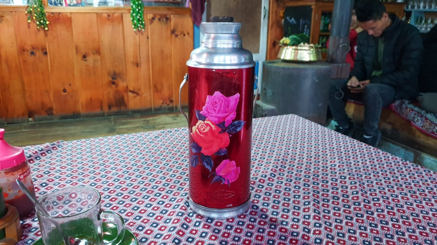 A thermos decorated with flowers on a table in a guesthouse