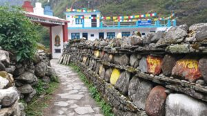 A colourful mani wall leading towards a gate in a village of Thonche