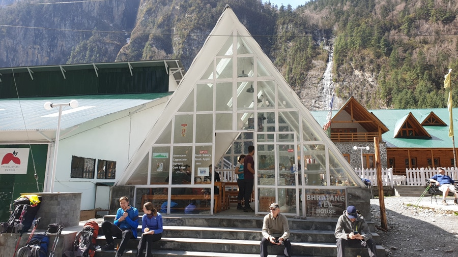 "A triangle-shaped glass building with people resting on its steps. SIgn reads ""Bhratang Tea House"""