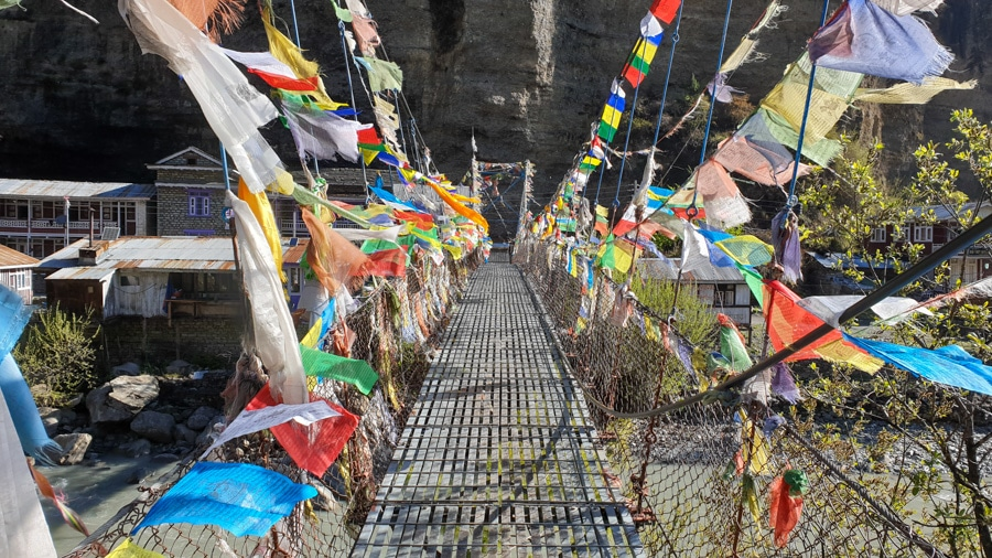 A suspension bridge adorned with colourful prayer flags fluttering in the wind