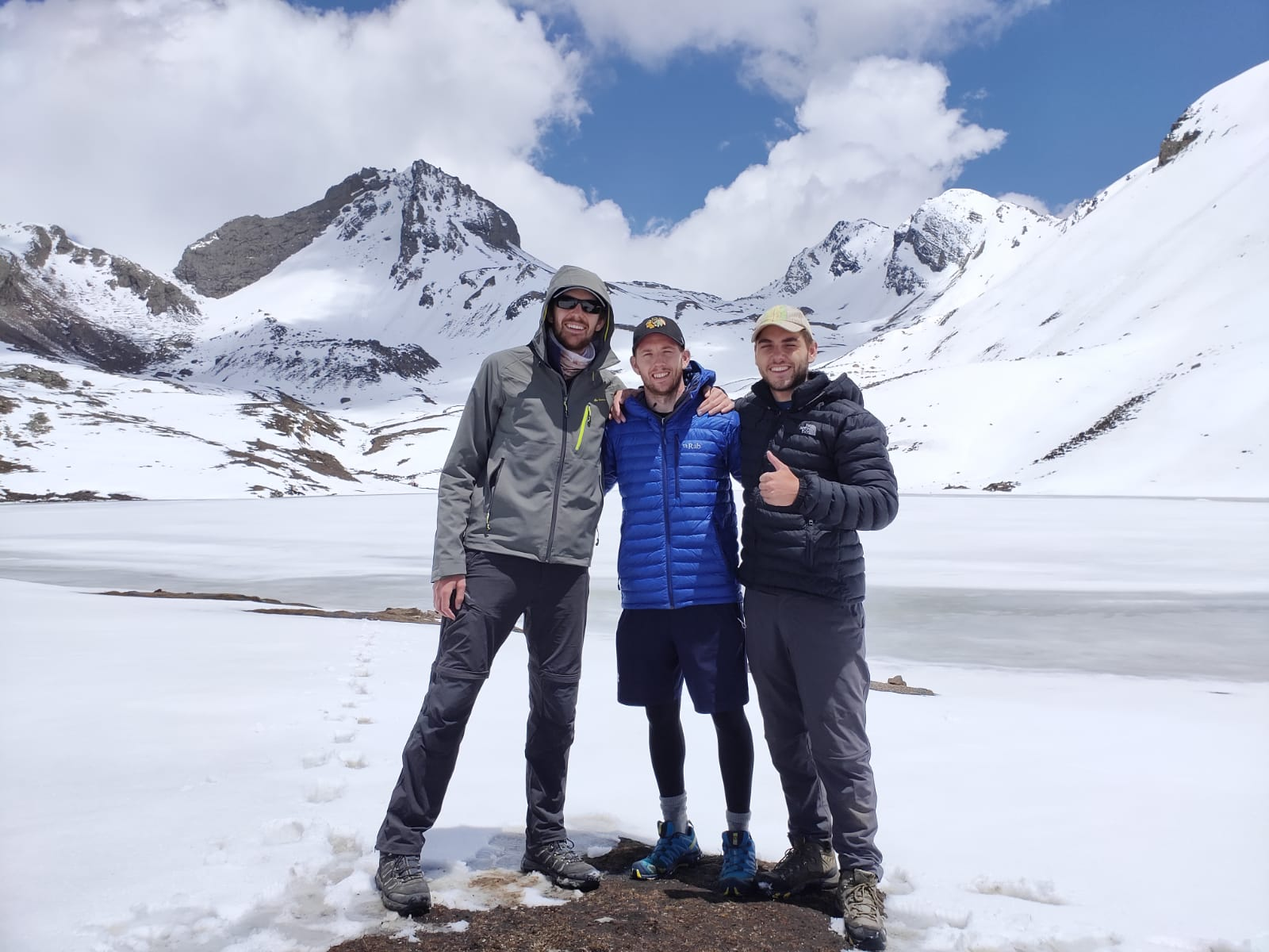 Three men pose in front of a frozen Ice Lake near Manang