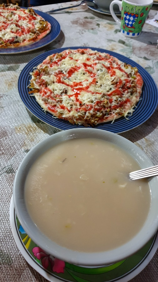 A bowl of soup and a pizza on a blue plate