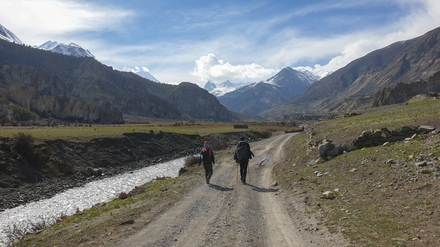 Hikers walking along an unpaved road from Lower Pisang to Manang