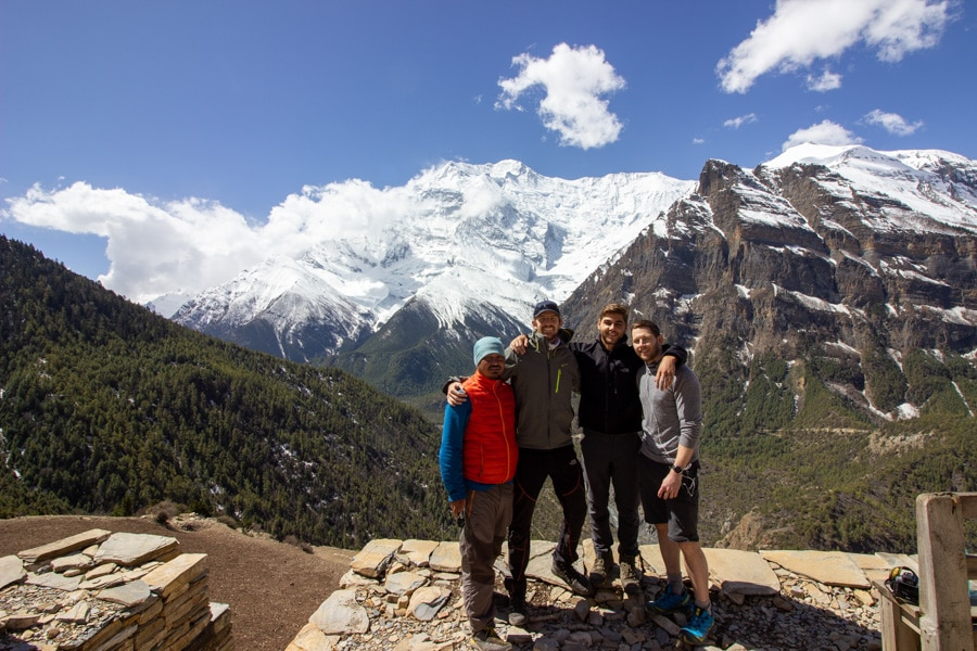 Four hikers posing for a photo at a lookout point overlooking mountains
