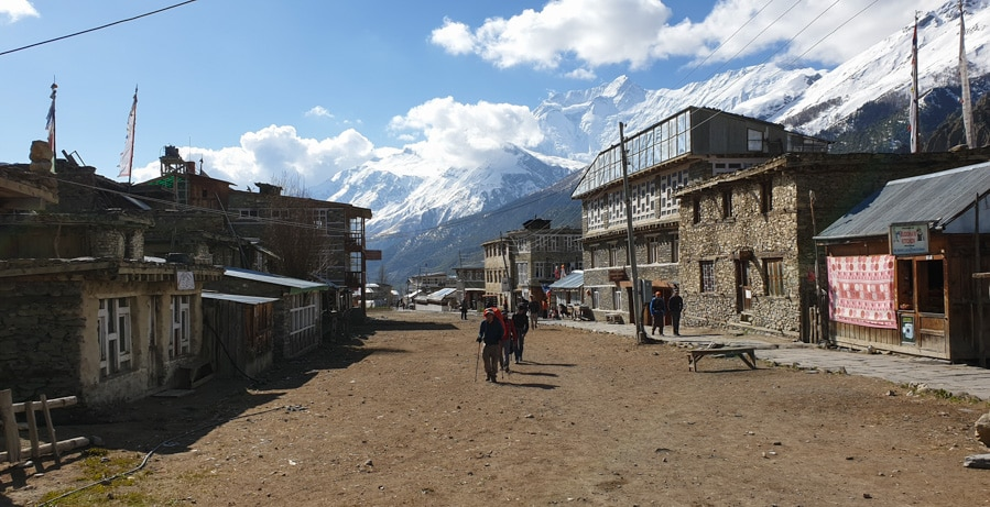 Wooded and stone buildings lining the main street in Manang