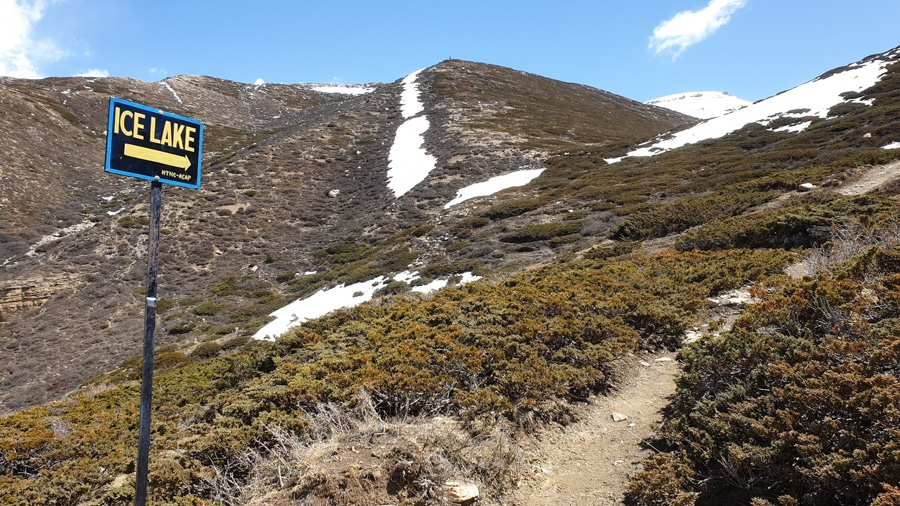 A sign pointing the way to Ice Lake among low shrubs and snow-covered slopes