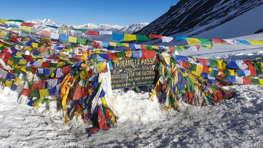 A sign for Thorang-La Pass surrounded by snow and colourful flags