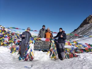 Four hikers posing for a photo at Thorang-La Pass sign surrounded by colourful flags