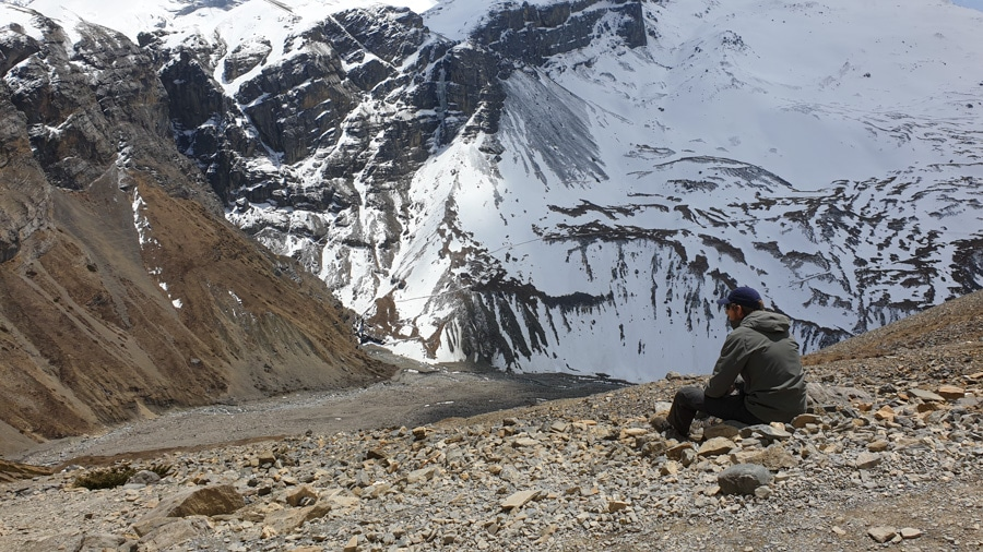 A man sitting on a rocky slope looking out towards mountains