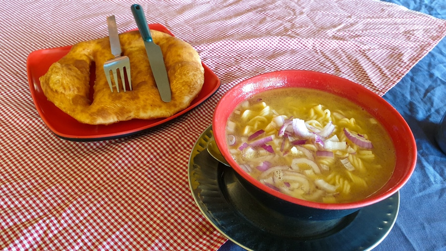 A bowl of soup with vegetables and a piece of bread with cutlery