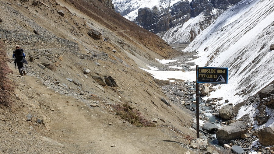 A hiker walking past a sign warning of landslides