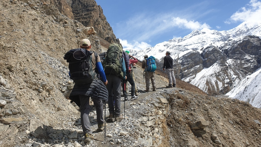 A group of hikers standing on a narrow trail