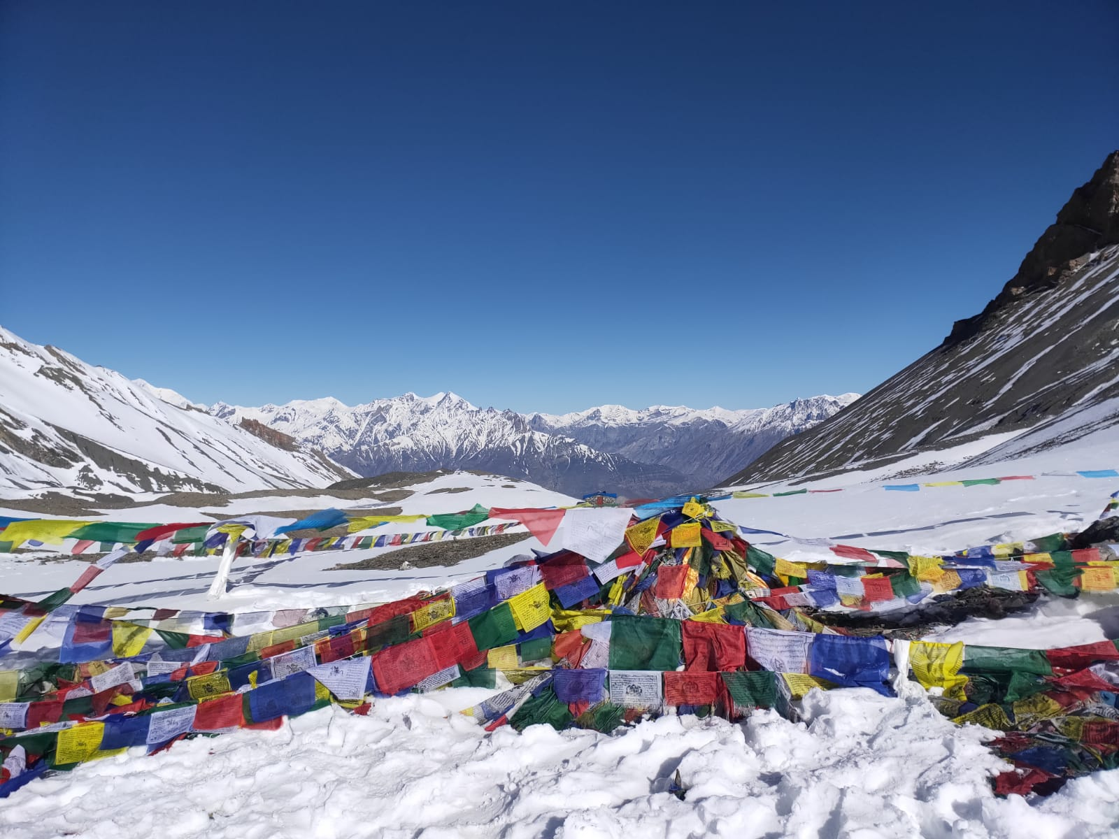 Thorong-La Pass prayer flags in the snow with mountains in the background