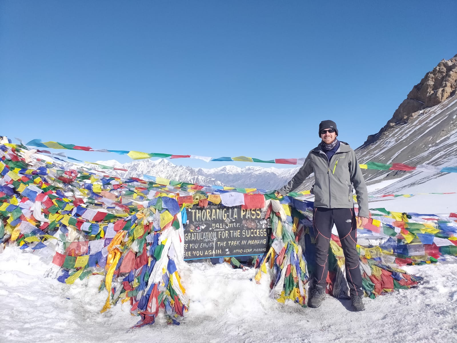 A man posing with a sign for Thorong-La Pass in Nepal surrounded by prayer flags