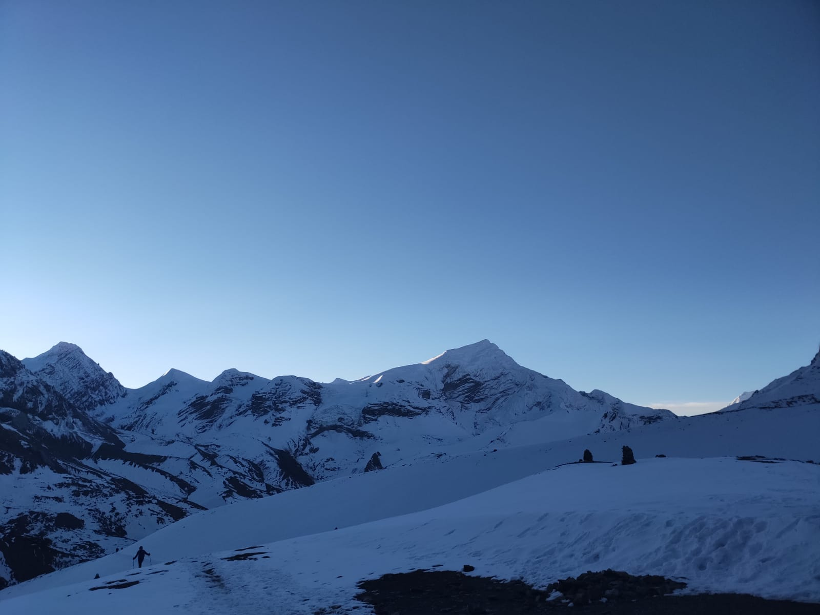 A hiker ascending a snow-covered path at dawn surrounded by mountains