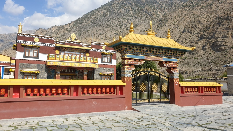An ornate golden entrance gate to a building in Jomsom