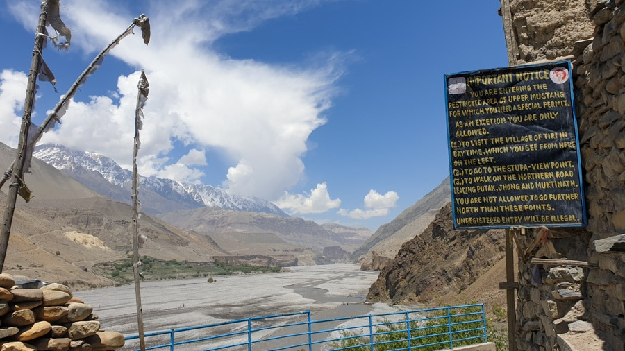 A sign overlooking a river and valley in Upper Mustang with a village in the distance
