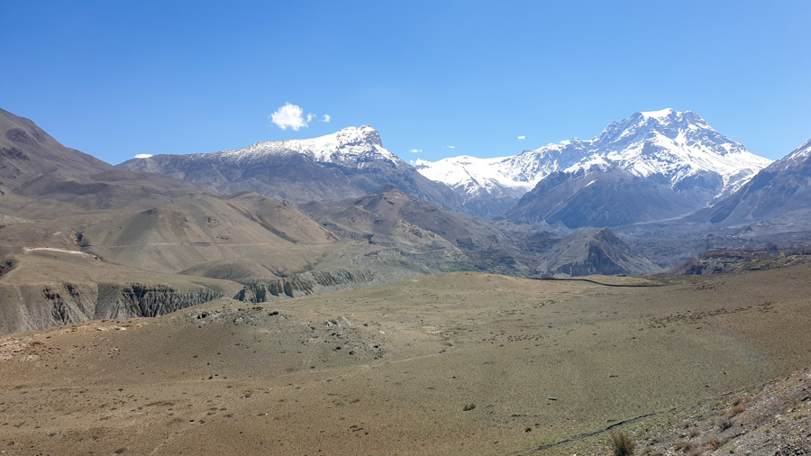 Arid hills framed by snow-capped mountains along the road from Muktinath to Jomsom