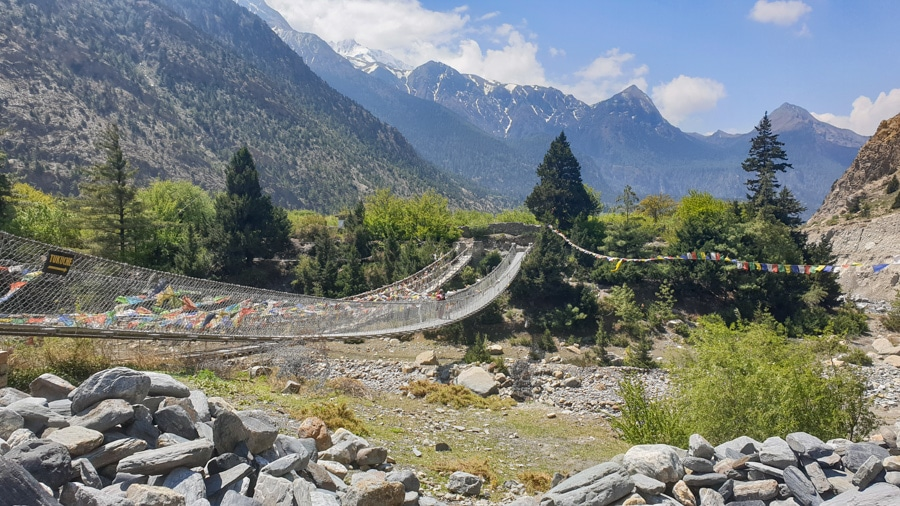 A suspension bridge over a dried up river bed between on a trail from Jomsom to Tukuche