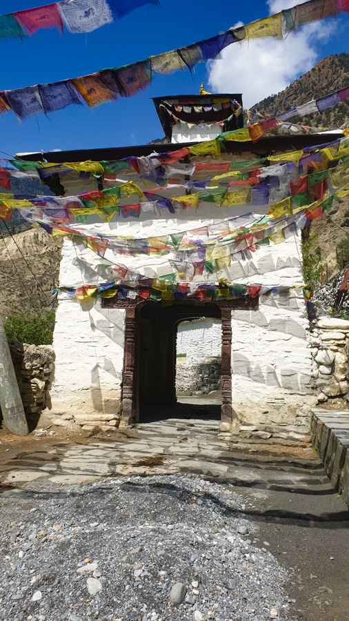 A large stone gate framed by colourful prayer flags on the trail from Jomsom to Tukuche