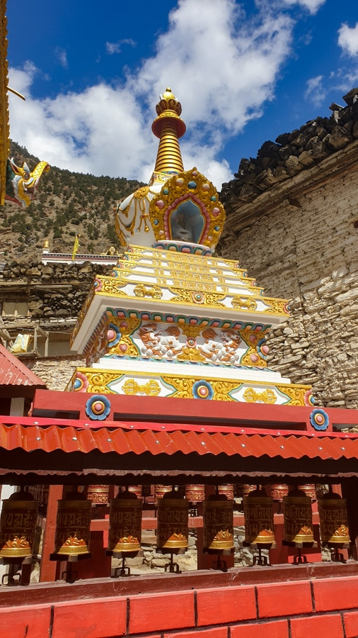 An ornate colourful stupa surrounded by prayer feels at its base