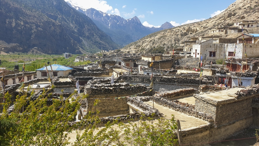 A view over the rooftops of a small village towards mountains
