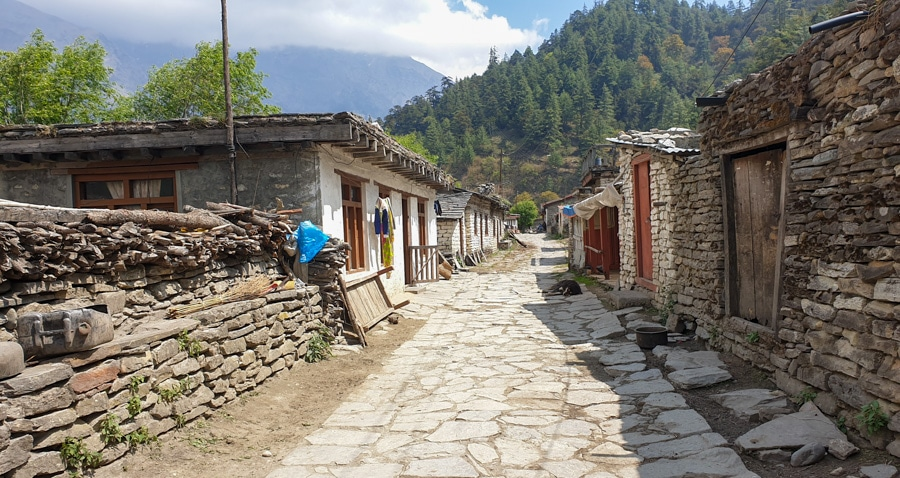 A path weaving between stone buildings in a village of Kokhethanti