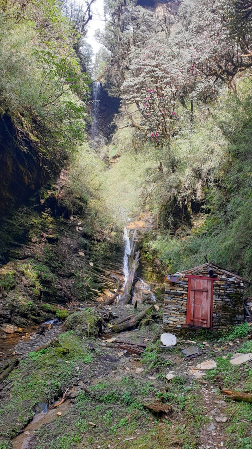 A small stone hut next to a waterfall in the rainforest